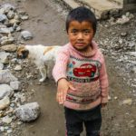 Nepalese child standing next to remaining ruins from the earthquake of April, 2015