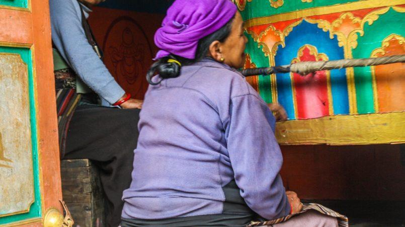 Two women spinning the praying wheel