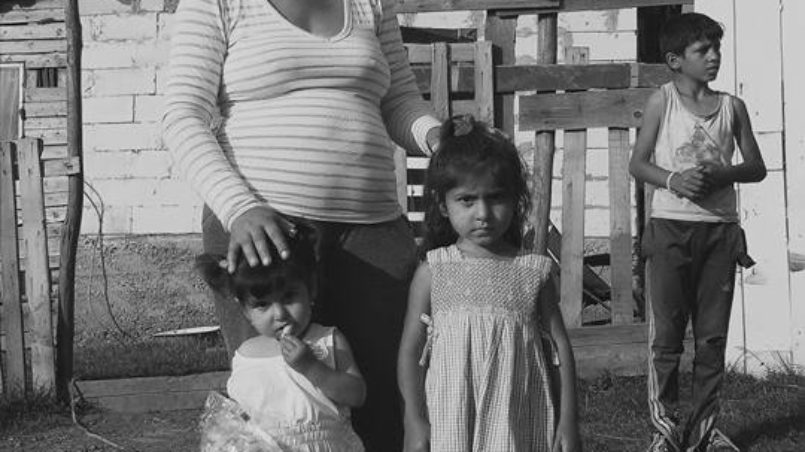 Mariana and her children in front of their house