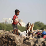 Street child in India plays with goat
